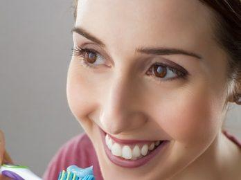 cepillo con dentrífico y mujer sonriendo.- Mujeres peor salud bucodental